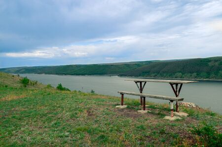 A wooden table and a bench stand on a steep cliff over a huge river against the backdrop of a mountain