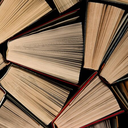 Books. Lots of colourful thick open books stand on a dark background. ready to read