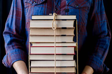 A man holds many multi-colored books tied with a rope