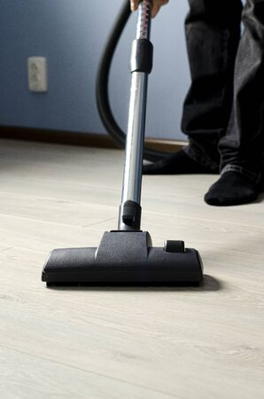 A man with a vacuum cleaner in his hands conducts cleaning in a room with blue walls and a light floor