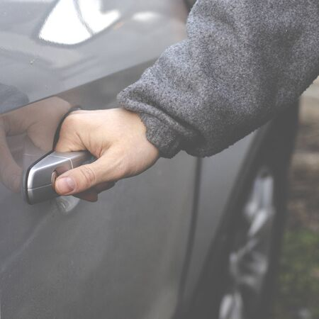 The man's hand opens the door of the silver-colored car. Close-up