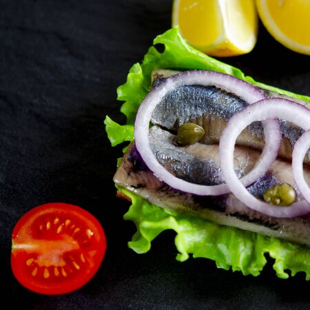 Herring fillet with salt, pepper, herbs, onion and lemon on black plate on white background. top view. healthy food