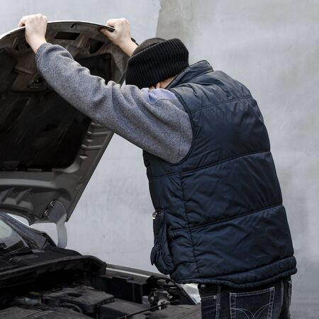 Car master opened the hood of a gray car for diagnosis and repair