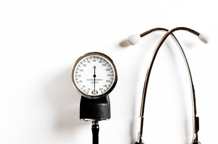 Concept for medicine. Vintage tonometer and stethoscope on white isolated background. View from above