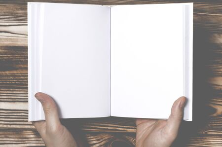 Men's hands holding open book with blank cover on light background. Mockup of open blank square book