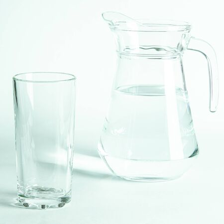 Pure clear water in a glass and jug stands on a white background. isolated
