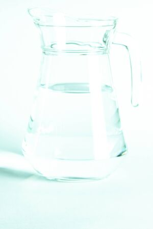 Blurred. Pure clear water in a glass and jug stands on a white background. isolated