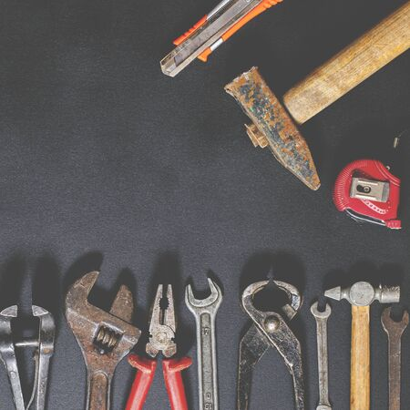 Hand tools for repair and reconstruction in home conditions lie on a black background. copy space
