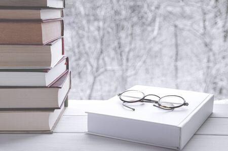 Old multi-colored books stand on a wooden shelf against the backdrop of the winter forest next to reading glasses Banque d'images