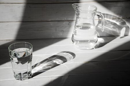 A glass of clean clear water stands on a white wooden background with sharp shadows. shadows