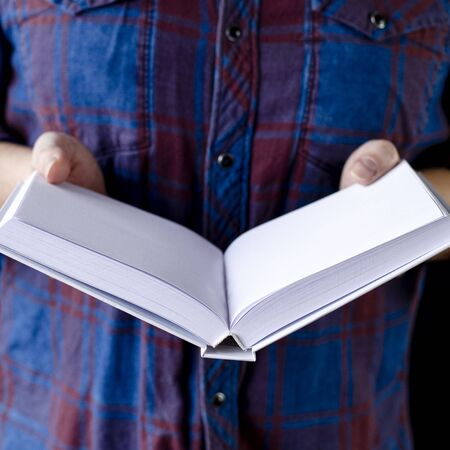 A mock-up of a white book in the hands of a man in a blue shirt. Close-up