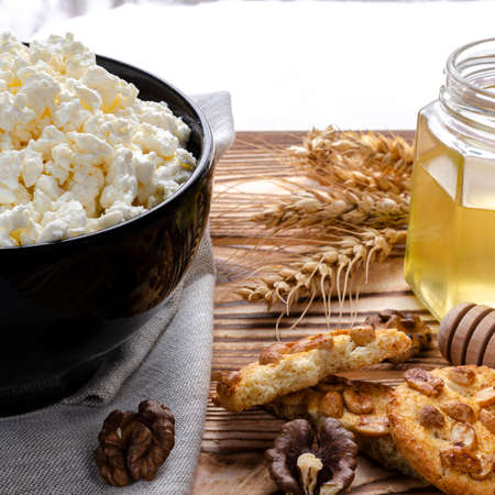 he textured curd lies in a black plate next to honey, homemade pastries and wheat ears