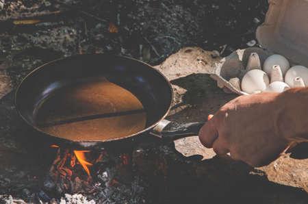 Mens hands prepare breakfast in a hike on a fire