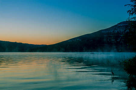 Dawn over a large mountain lake covered with fog against the backdrop of mountain peaks.