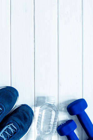 Sports set. Blue womens sneakers, blue dumbbells and white scales stand on a white background Stockfoto