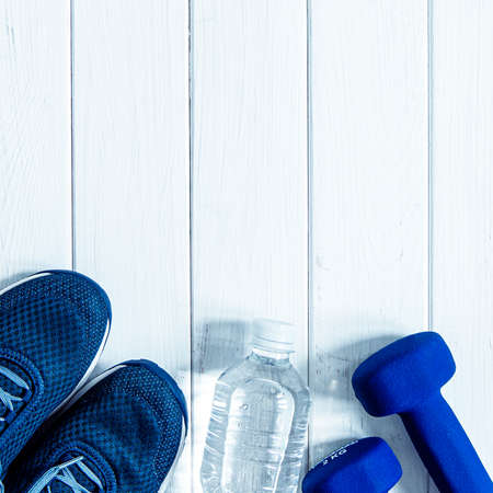 Healthy lifestyle. sneakers, dumbbells and a bottle of water on a white wood background Stockfoto