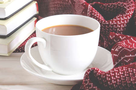 A cup of coffee, a warm scarf and books stand on a white wooded background