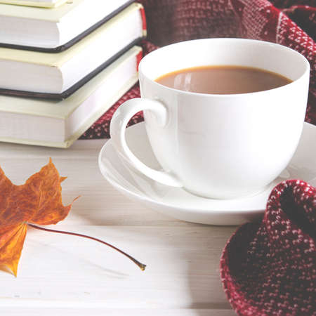 A cup of coffee with milk stands on the table next to books and a warm wool scarf Stockfoto