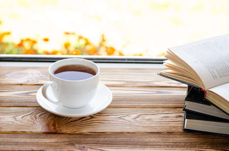A cup of tea stands on a window sill against the window