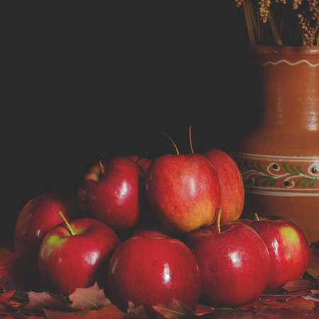 Red juicy apples lie on the table on yellow autumn leaves