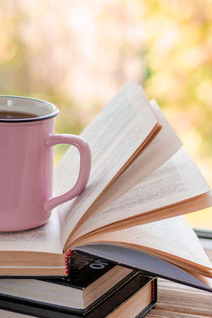 A pink cup of tea stands on a pile of open books
