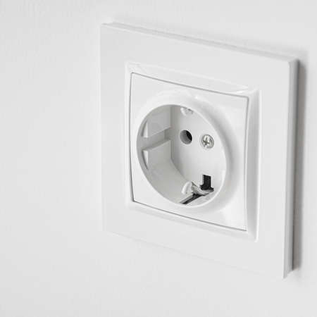 The white plastic socket is mounted in a white wall