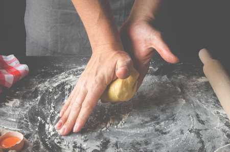 The mans hands knead the dough for the preparation of cherry strudel Stockfoto