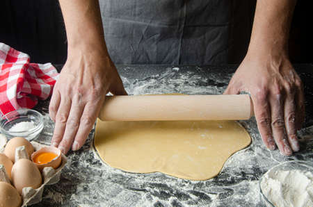 The mans hands prepare the dough for the preparation of pizza and home baking Stockfoto