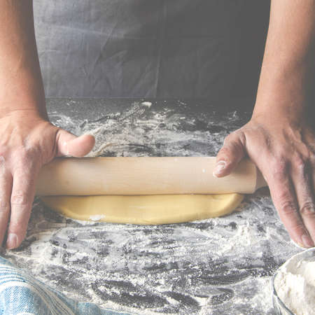 Cook hands kneading dough, sprinkling piece of dough with white wheat flour Stockfoto