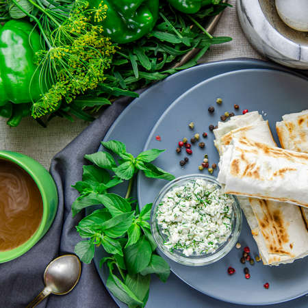 Healthy breakfast. Green vegetables. Pita bread with cheese and dill lie on round gray plates next to greens and a cup of coffee