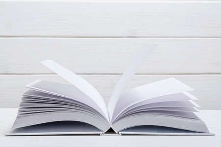 White new open book with clean empty pages lies on a wooded table