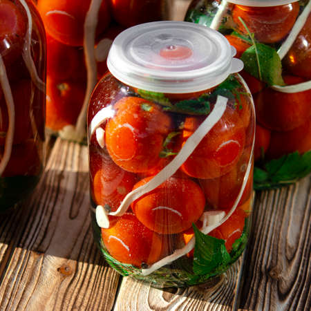 Autumn harvest of red tomatoes and garlic in jars for preservation