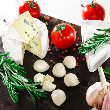 Cheese assorted with vegetables and rosemary lie on a dark board