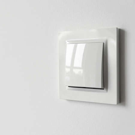 A white plastic power switch in an apartment on a white wall. Repair Stock fotó