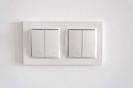 White plastic pass-through electricity switches on a white wall. Repair
