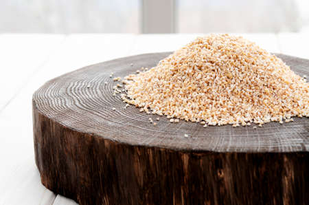 A healthy way of life. Coarse barley grits on a round wooden board