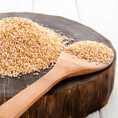 Burlap sack with pearl barley spilling out over a white background