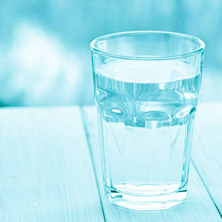 A glass with pure clear melt water stands on a white wood table