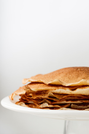 Golden wheat pancakes or crepes in a white plate