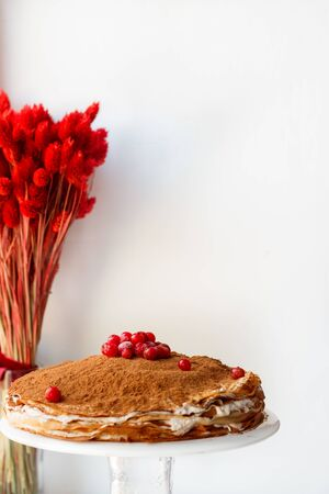 Crepe cake with butter cream and cocoa and redcurrant on a white background with dried flowers