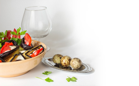 composition of eggplant with tomatoes in a ceramic bowl, glasses of brandy and quail eggs