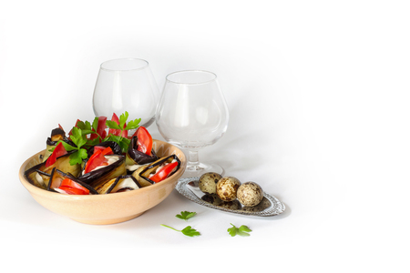 appetizer: Tasty vegetable appetizer of tomatoes, eggplant white sauce on the background , quail eggs and glasses for drinks