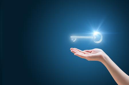 Ręka wspiera klucz do sukcesu w biznesie. Skład z pustą przestrzenią po lewej.
