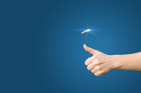 coin toss: Hand throws a coin on a blue background for decision-making