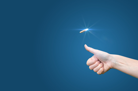 hand throws a coin on a blue background to make the decision Stock Photo