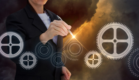 Businesswoman draws gears in the sky.