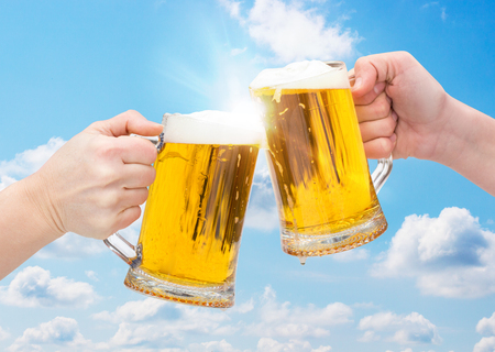 Clinking Beer glasses on sky background