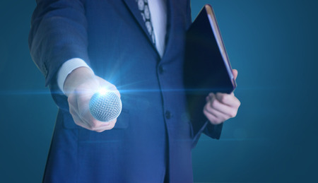 Businessman holds out the microphone to speak. Stock Photo