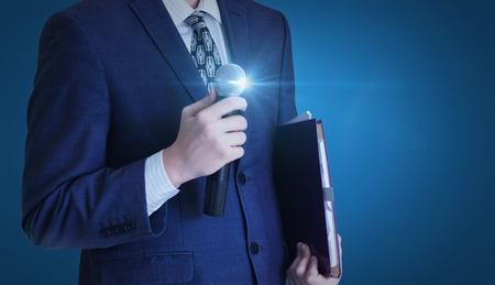 Businessman stands with a microphone. Standard-Bild