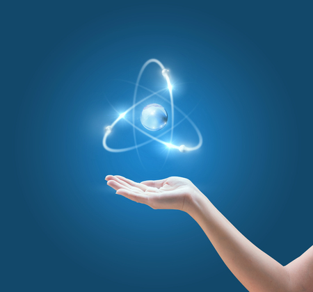 Hand with the atom image on blue background. Banco de Imagens - 71278699
